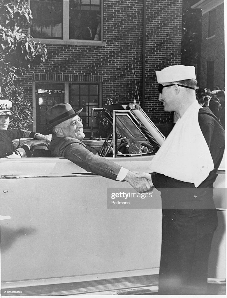 President Franklin Delano Roosevelt gives a hearty handshake and a warm smile to a wounded sailor during a visit to the Puget Sound Naval Shipyard in...
