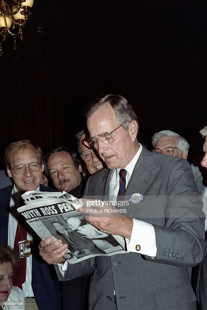 US President George Bush examines on July 2, 1992 a weekly tabloid newspaper carrying an article claiming a space alien has met with undeclared presidential candidate Ross Perot and also with President Bush at Camp David. The President was on a visit to Capitol Hill to promote health care reform.