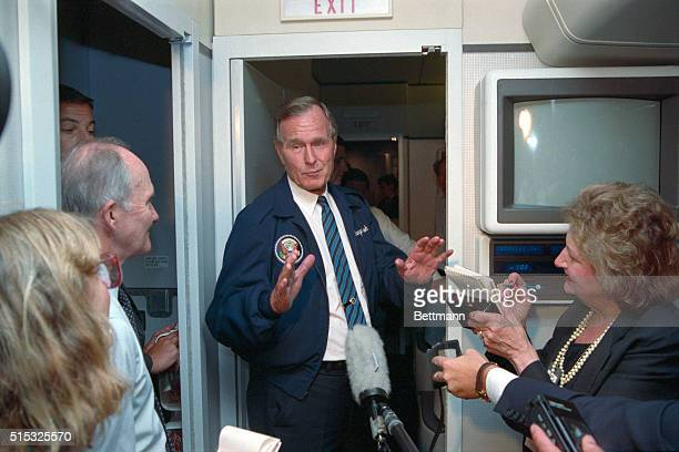 President George Bush gestures as he chats with reporters aboard Air Force One en route to Washington after a summit meeting with Soviet President...