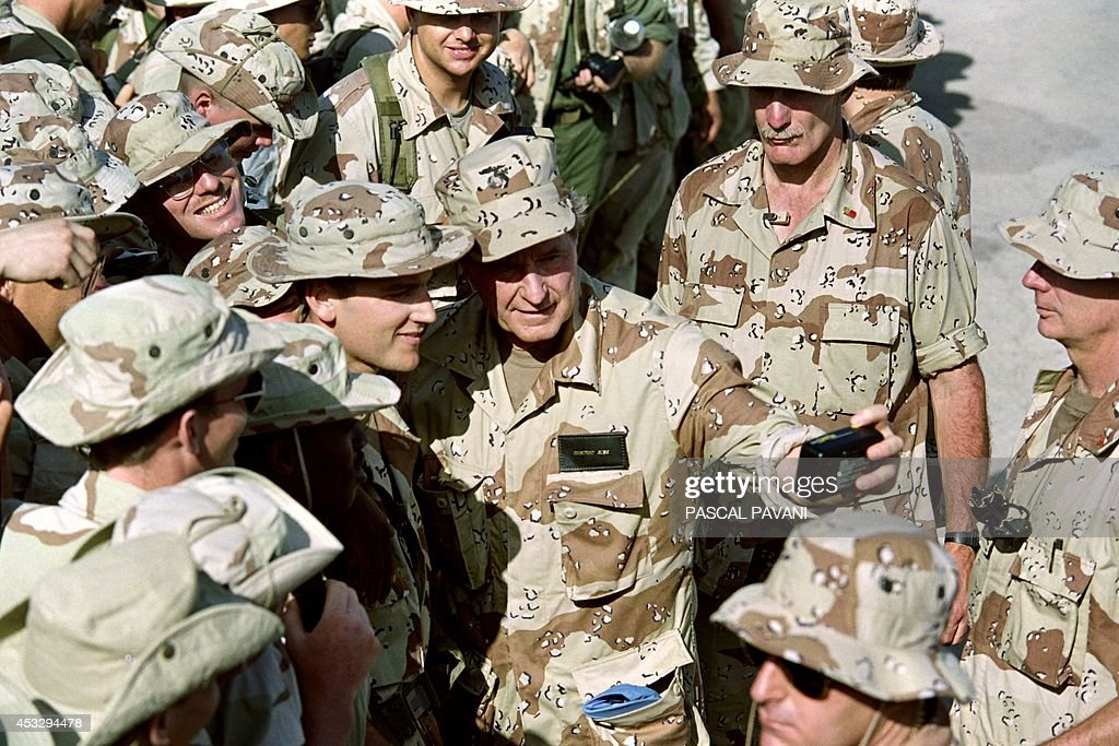 US President George Bush holds an Instamatic camera on January 1, 1993 as he snaps a picture of himself with a Marine at the Mogadishu airport. Bush ends his visit to Somalia early tomorrow and flies to Russia.