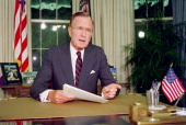US President George Bush poses for photographers after his address to the nation 27 September 1991 in the Oval Office of the White House During his...