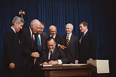 President George Bush signs the 1990 Farm Bill into law He is joined by Senators Richard Lugar Patrick Leahy and Bob Dole and Agriculture Secretary...