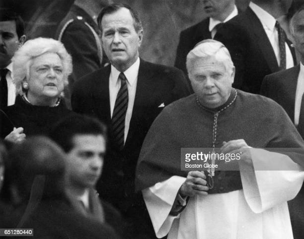 President George HW Bush center First Lady Barbara Bush left and Cardinal Bernard Law enter St Joseph's Church in Lincoln Mass for the funeral of...