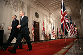 President George W Bush and British Prime Minister Tony Blair walk down the Cross Hall prior to holding a press conference in the East Room of the...