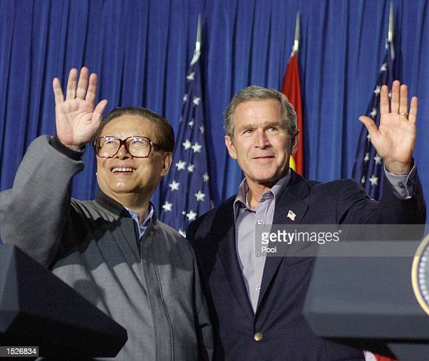 S President George W Bush and Chinese President Jiang Zemin wave following a joint news conference October 25 2002 at the Bush ranch in Crawford...