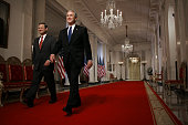 US President George W Bush and federal appeals court judge John Roberts walk past a portrait of Ronald Reagan as they arrive to announce Roberts'...