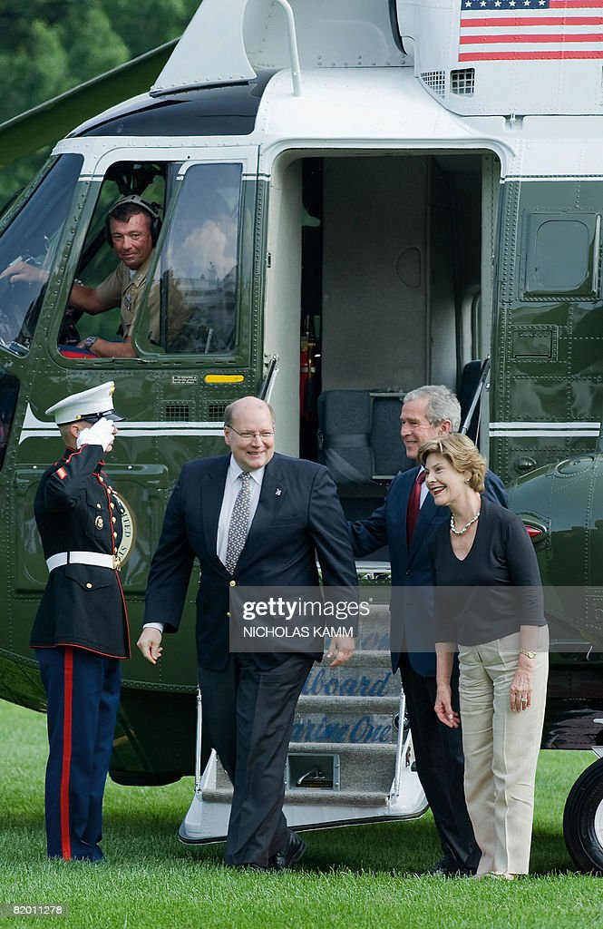 US President George W. Bush and First Lady Laura Bush show the way to outgoing US White House Deputy Chief of Staff Joe Hagin to greet wellwishers who came to bid him farewell as he arrived aboard presidential helicopter Marine One on the South Lawn of the White House in Washington on July 20, 2008. Bush spent the weekend at his ranch in Crawford, Texas. AFP PHOTO/Nicholas KAMM