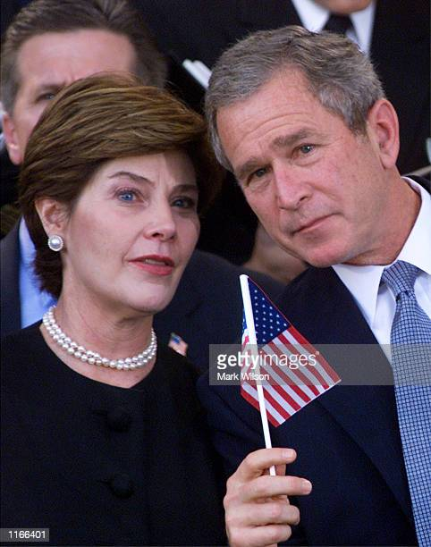 S President George W Bush and First Lady Laura hold an American flag during a Memorial Service for terrorsit attack victims October 11 2001 at the...