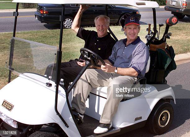 S President George W Bush and his golf partner Mike Woods ride back to the club house after playing 18 holes of golf at Andrews Air Force Base July...