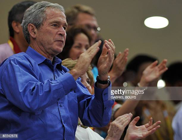US President George W Bush applauds as he attends the men's preliminary round group B basketball match between USA and China at the Olympic...