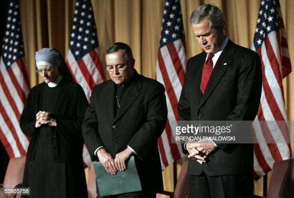 President George W Bush bows his head with Sister Minereche and Archbishop of Denver Charles Chaput during an opening prayer at the National Catholic...