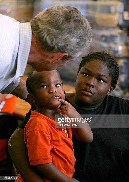 US President George W Bush consoles two hurricane Katrina victims while visiting a food distribution center in Gulfport MS 12 September 2005...