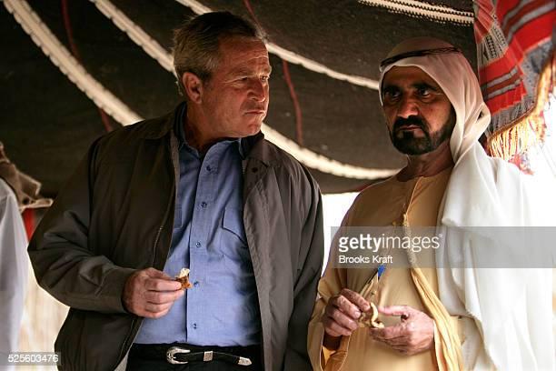 US President George W Bush eats handmade bread with United Arab Emirates Vice President Mohammed bin Rashid Al Maktoum during a visit to the Royal...