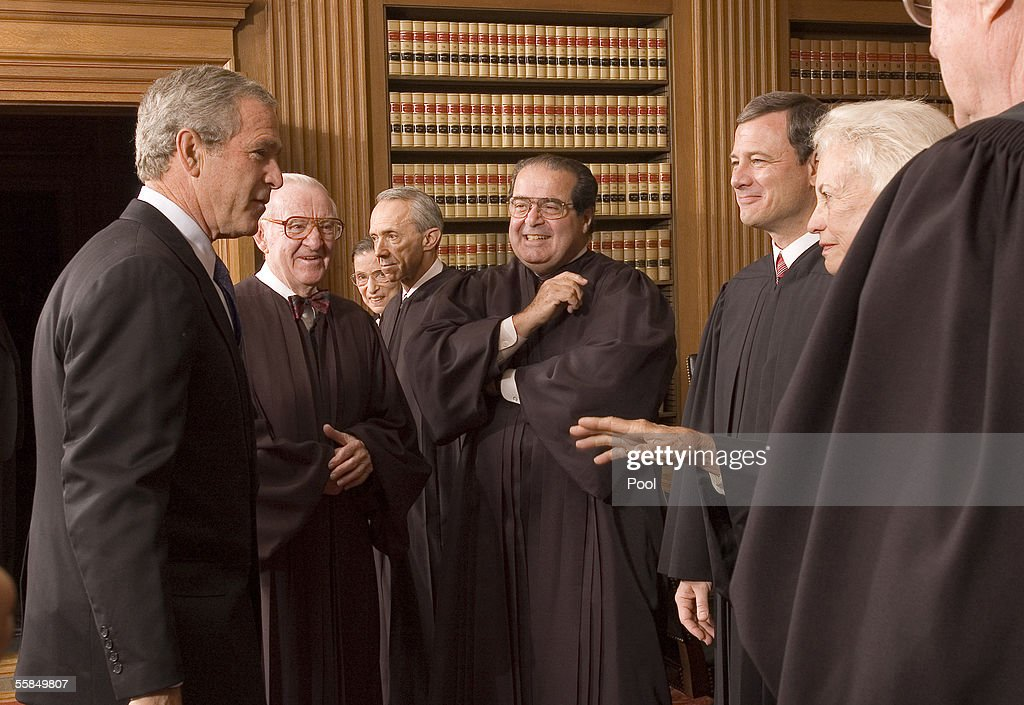 U.S. President George W. Bush (L) enjoys a light moment with Supreme Court Justices (L-R), John Paul Stevens, Ruth Bader Ginsburg, David H. Souter, <a gi-track='captionPersonalityLinkClicked' href=/galleries/search?phrase=Antonin+Scalia&family=editorial&specificpeople=215620 ng-click='$event.stopPropagation()'>Antonin Scalia</a>, Chief Justice John Roberts and Justice Sandra Day O'Connor in the Chief Justice Conference Room October 3, 2005 at the Supreme Court in Washington, DC. Replacing William H. Rehnquist, who died last month at age 80, Roberts will take his seat at the helm of the high court on the opening day of the 2005-06 term as the first new justice in more than 10 years and its first new chief in almost 20.