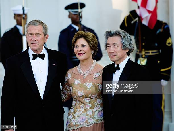 S President George W Bush first lady Laura Bush and Japanese Prime Minister Junichiro Koizumi pose for pictures in the North Portico of the White...
