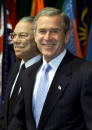 S President George W Bush flanked by Secretary of State Colin Powell smiles before speaking at the State Department October 4 2001 in Washington DC