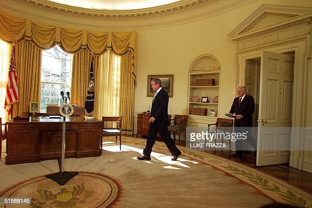 President George W Bush followed by US Vice President Dick Cheney walks into the Oval Office of the White House 26 January 2001 in Washington DC for...