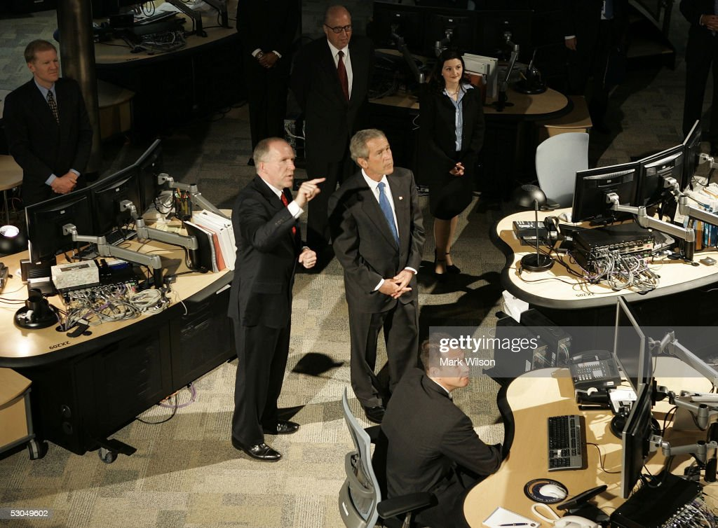 U.S. President George W. Bush (C) gets guided tour of the National Counterterrorism Center from Interim Director John Brennan June 10, 2005 in Tysons Corner, Virginia. Bush is pushing Congress for the renewal of the Patriot Act anti-terrorism laws.