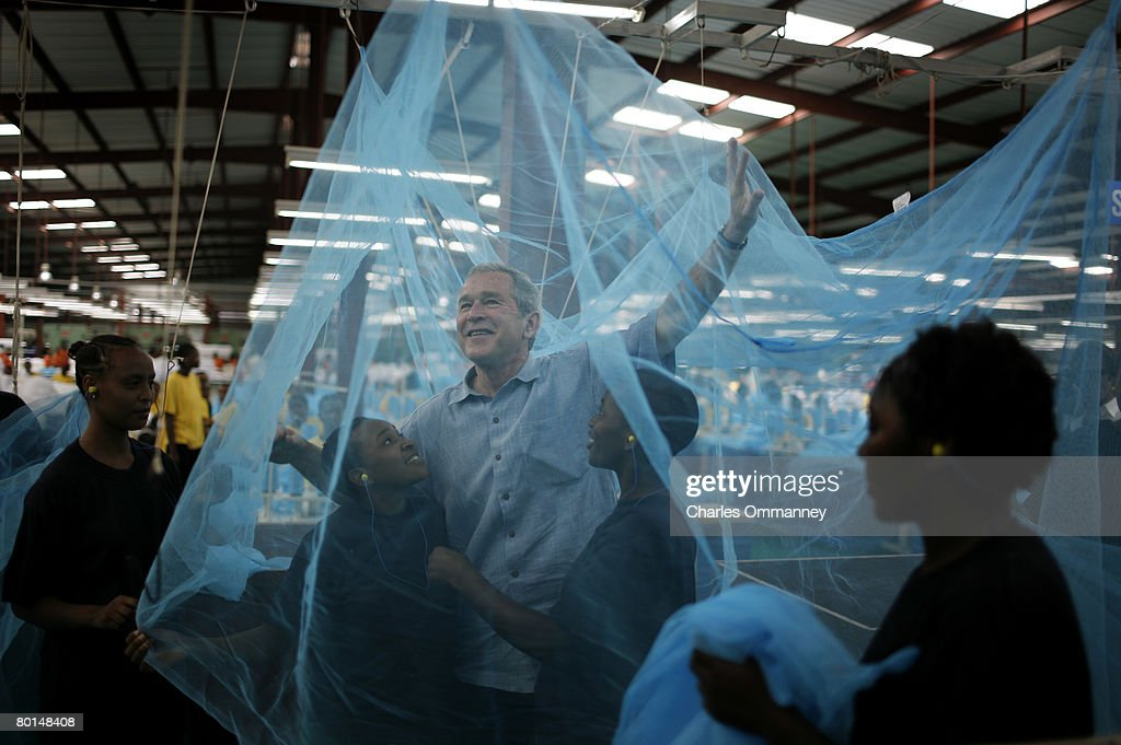 US President George W. Bush greets workers under a mosquito bed net during a tour of the A to Z Textile Mills on February 18, 2008 in Arusha, Tanzania. The company produces insecticidal bed nets, which help in the prevention of malaria. The company produces insecticidal bed nets which help in the prevention of malaria. The US president has used his visit -- which began in Benin on February 16, 2008, and will take him to Rwanda, Ghana and Liberia before he heads back to Washington -- to highlight US-African cooperation to battle disease and poverty.