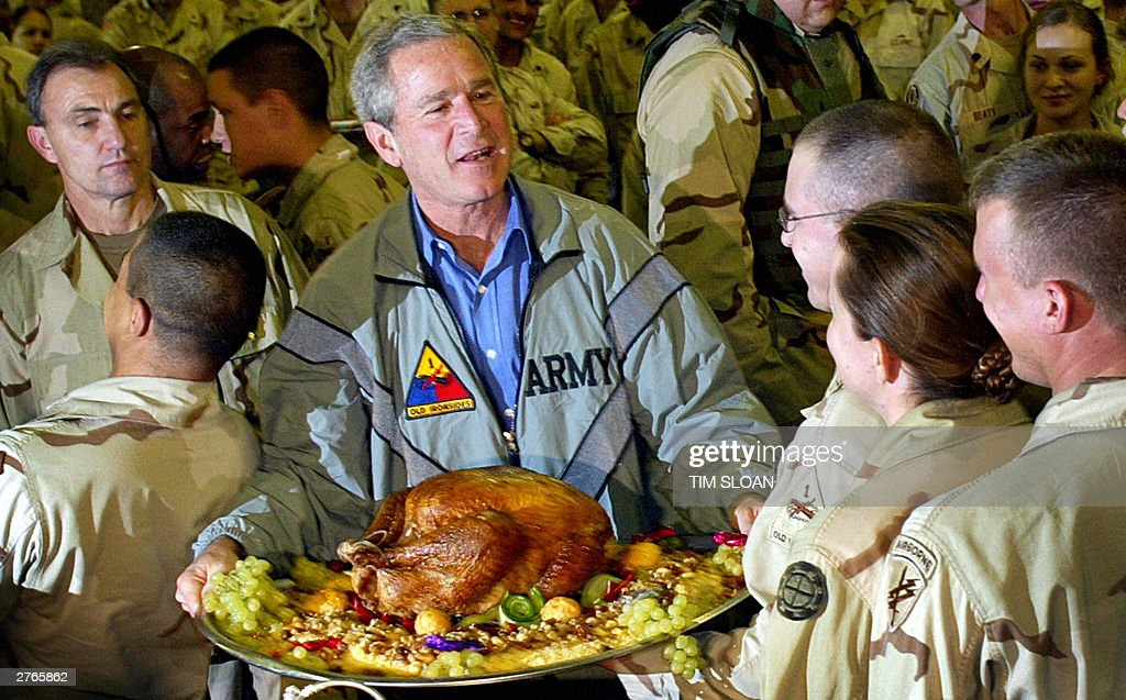 US President George W. Bush holds a Thanksgiving turkey for US troops stationed at Baghdad International Airport 27 November, 2003 in Baghdad, Iraq. Under unprecedented secrecy, the President was flown without public knowledge from Waco, Texas, to Washington, DC, where he changed planes then onto Iraq where he spent two and a half hours on the ground to salute US troops on the US Thanksgiving Holiday.