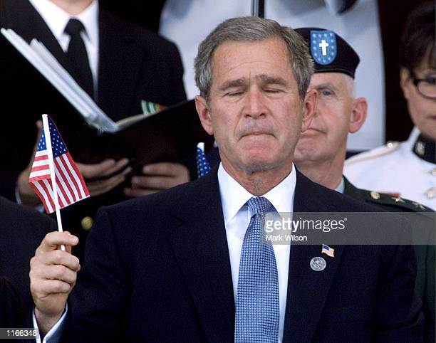 S President George W Bush holds an American flag during a Memorial Service at the Pentagon October 11 2001 in Arlington VA