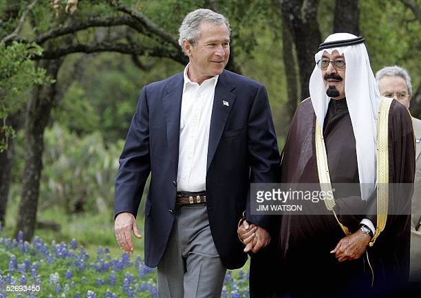 President George W Bush holds hands with Saudi Crown Prince Abdullah while walking past some blue bonnets at his Crawford ranch 25 April 2005 Bush...