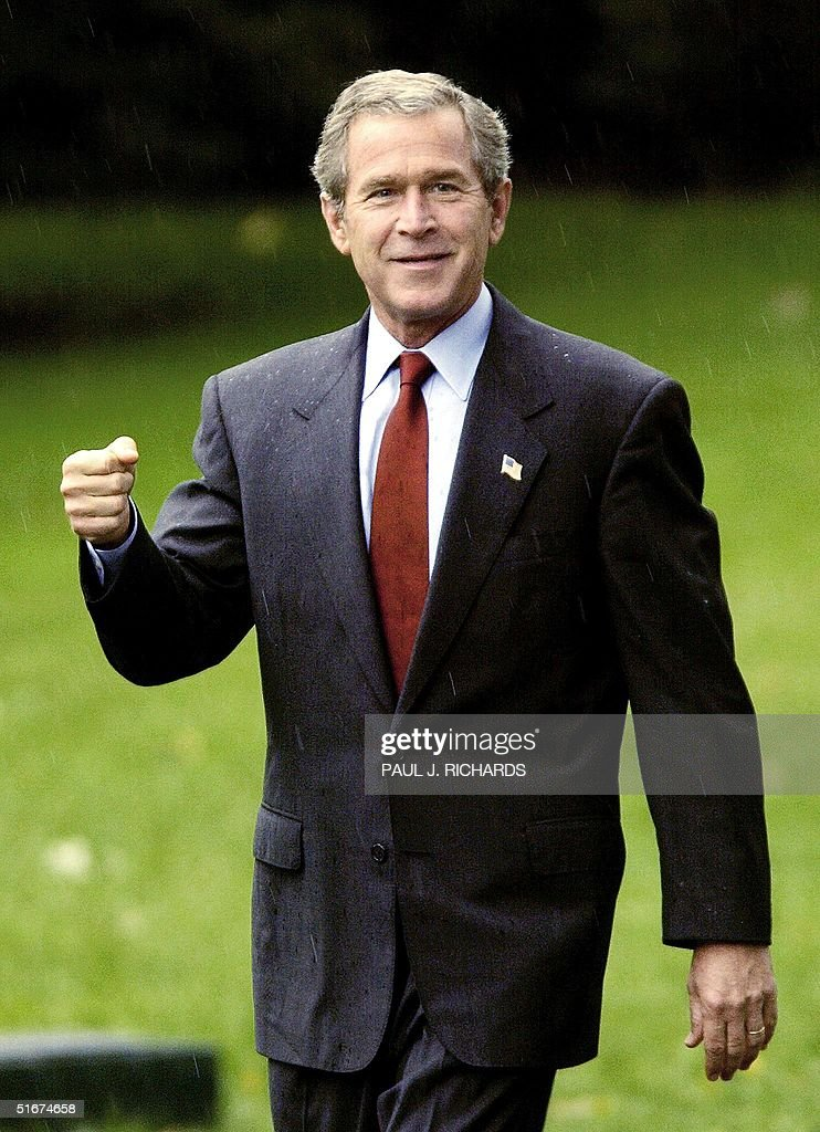 US President George W. Bush imitates holding an umbrella as light showers caught him by surprise as he walks towards Marine One 16 September 2002 on the South Lawn of the White House and then a short flight to Air Force One. The President will spend the day in Davenport, Iowa, touring Sears Manufacturing, deliver remarks on the economy and fiscal restraint, and attend a fund raising luncheon for Jim Nussel for Congress. AFP PHOTO/Paul J. Richards