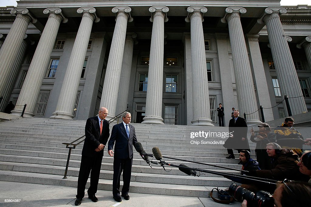 S President George W Bush is joined by Treasury Secretary Henry Paulson while making a statement to the news media after a meeting at the Treasury...