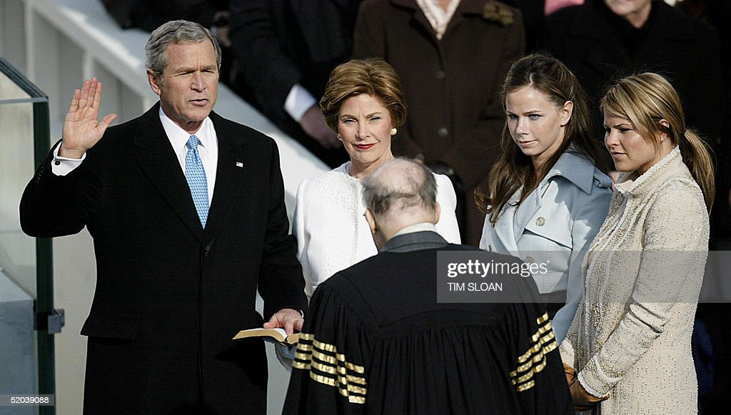 US President George W. Bush (L) is sworn in for his second term 20 January, 2005, on the west side of the US Capitol, by Supreme Court Chief Justice Willian Rehnquist (back to the camera). Bush was joined on stage by his twin daughters Jenna (R) and Barbara (2nd-R) and by his wife US First Lady Laura Bush. AFP PHOTO / TIM SLOAN