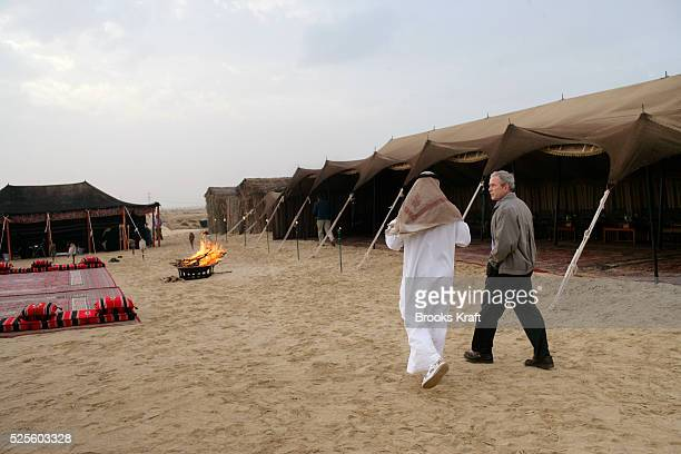 US President George W Bush is welcomed by Abu Dhabi Crown Prince Sheikh Mohammed Bin Zayed Al Nahyan to his desert encampment near Sowaihan in the...