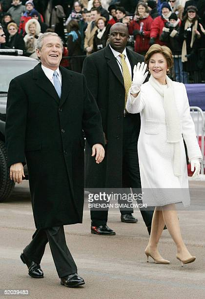 President George W Bush laughs while walking down Pennsylvania Avenue with First Lady Laura Bush during the Inaugural Parade 20 January 2005 in...