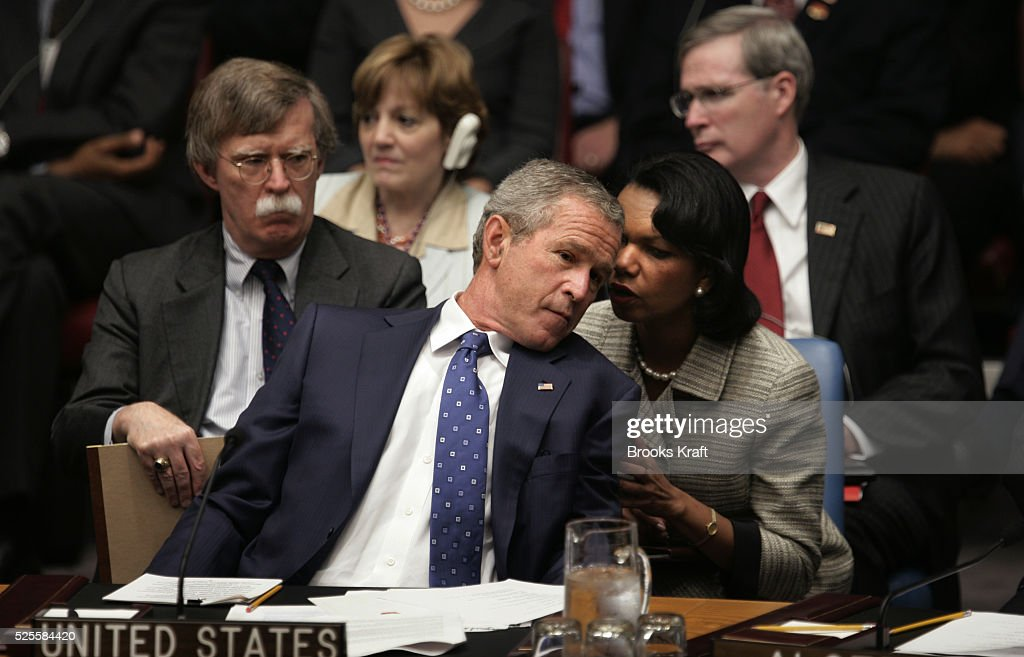 US President George W Bush leans back to confer with Secretary of State Condoleezza Rice as US Ambassador to the UN John Bolton watches at a Security...