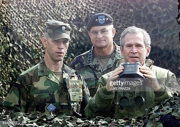 President George W Bush looks across the demilitarized zone into North Korea through a bullet proof glass from Outpost Ouellette a US Military base...