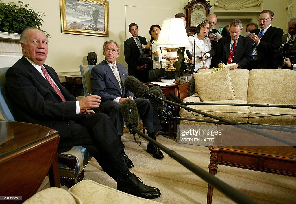US President George W. Bush (R) meets with Chile's President Ricardo Lagos (L) in the Oval Office of the White House 19 July, 2004 in Washington, DC. Bush and Lago were to discuss democracy and trade in Latin American, notably on the free trade agreement between the two countries that took effect 01 January. Since the deal, Chile's exports to the United States have jumped by 13 percent, while US exports to Chile rose 13 percent. AFP Photo/Stephen JAFFE