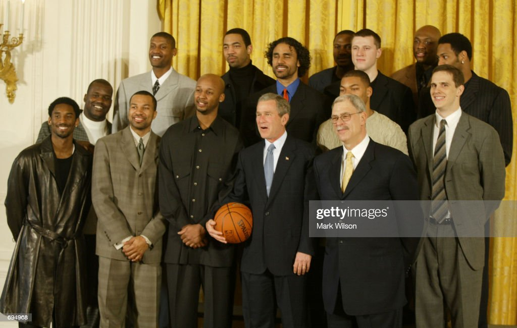 U.S. President George W. Bush poses with the Los Angeles Lakers basketball team during a ceremony honoring the team for their 2001 NBA championship title January 28, 2002 at the White House in Washington DC.