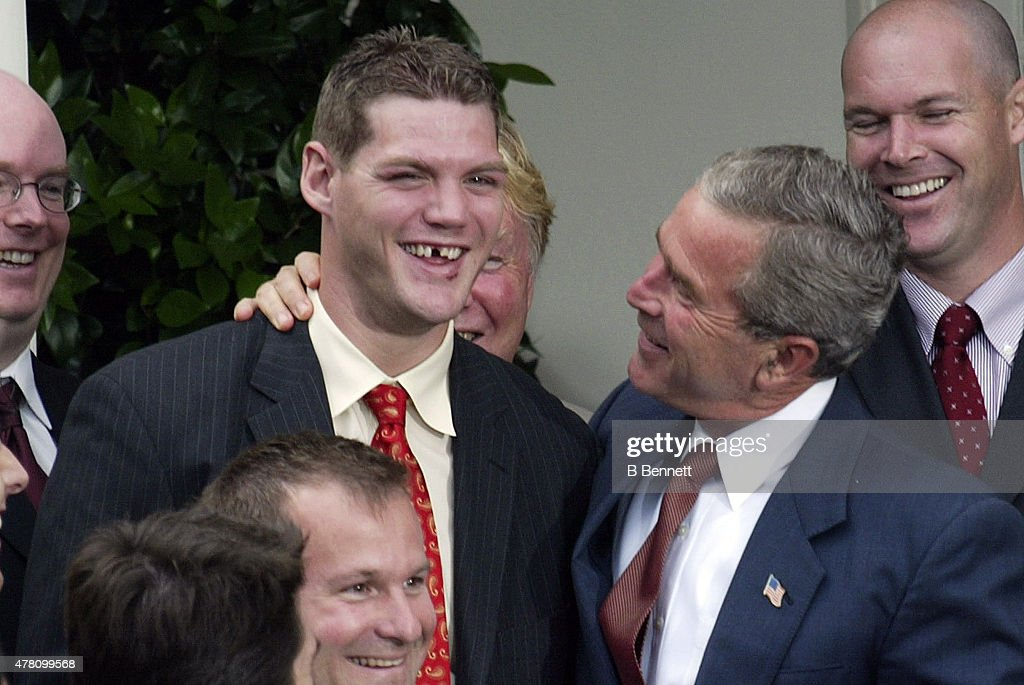 President George W Bush puts his arm around NHL New Jersey Devils defenseman Colin White for a quick photo as unidentified members of the team look...