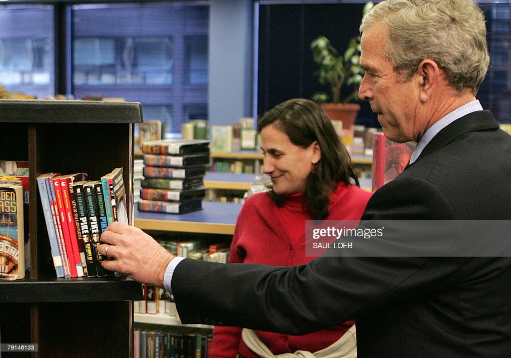 US President George W. Bush (R) reaches for a book alongside a library volunteer during a tour of the Martin Luther King, Jr. Memorial Library to observe Martin Luther King, Jr. Day in Washington, DC, 21 January 2008.