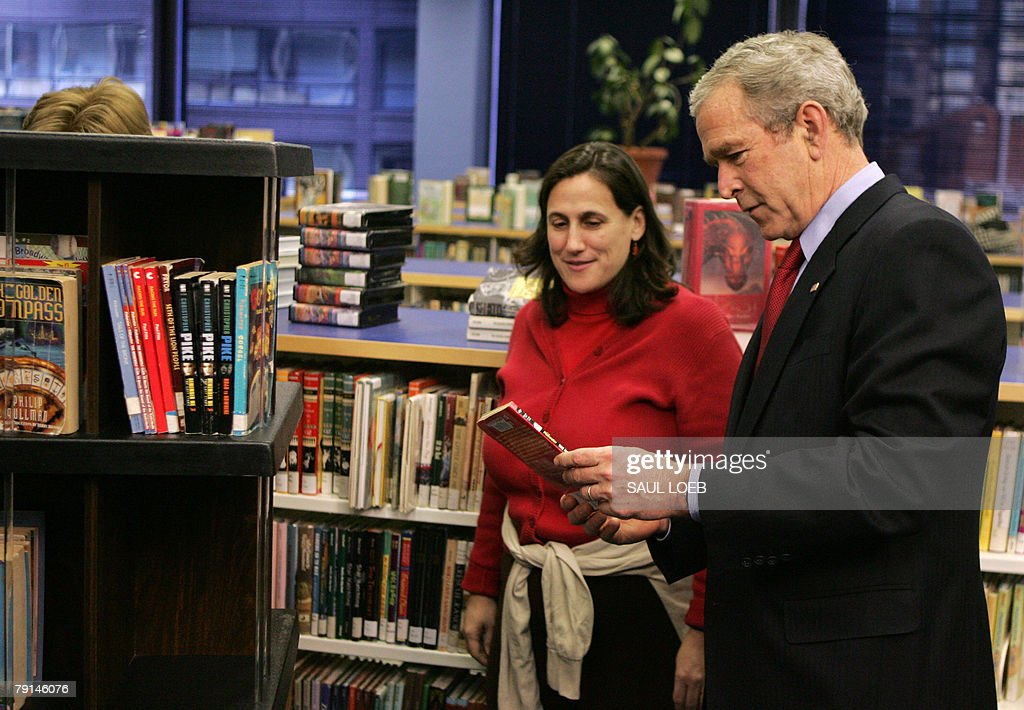 US President George W. Bush (R) reads a book alongside a library volunteer during a tour of the Martin Luther King, Jr. Memorial Library to observe Martin Luther King, Jr. Day in Washington, DC, 21 January 2008.