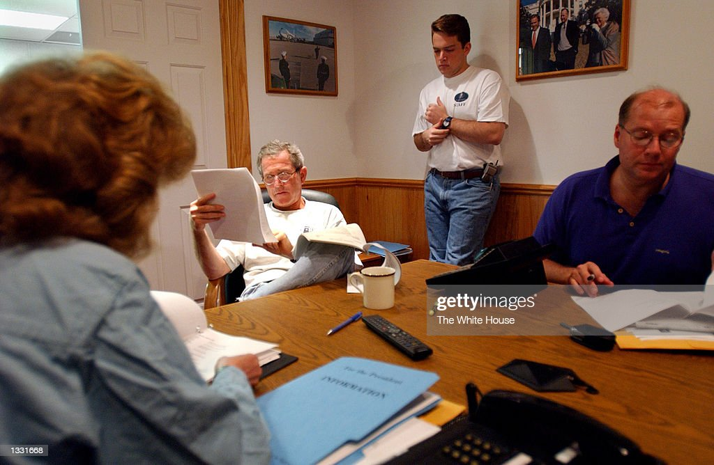 U.S. President George W. Bush reads over paperwork during a White House staff meeting inside a telecommunications trailer his ranch August 9, 2002 in Crawford,Texas. Bush is working from his 1,600-acre ranch in Texas for about a month. Also shown (from L) are Staff Secretary Harriet Miers, personal assistant Blake Gottesman and Deputy Chief of Staff Joe Hagin.