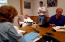 S President George W Bush reads over paperwork during a White House staff meeting inside a telecommunications trailer his ranch August 9 2002 in...