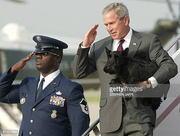 President George W Bush salutes upon arrival at Andrews Air Force Base in Maryland carrying his dog Barney from Air Force One 29 July 2004 Bush spent...