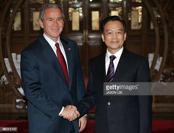 President George W Bush shakes hands with Chinese Premier Wen Jiabao at the Diaoyutai State Guest House in Beijing 20 November 2005 Bush earlier told...