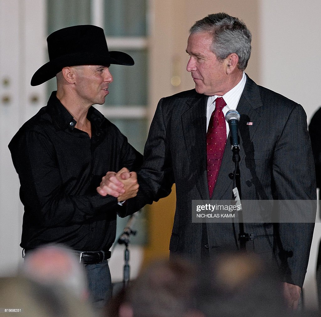 US President George W. Bush (R) shakes hands with country singer Kenny Chesney (C) after giving a performance in the Rose Garden at the White House following a dinner in honor of Major League Baseball on July 16, 2008. AFP PHOTO / Nicholas KAMM