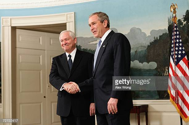 US President George W Bush shakes hands with Defense Secretary Nominee Robert Gates after he spoke to the media in the Diplomatic Reception Room of...