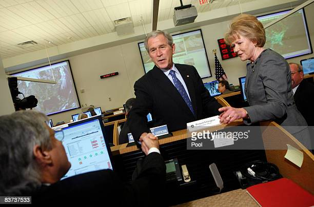 US President George W Bush shakes hands with information officer Robert Ellington during a visit to the US Department of Transportation with Mary E...