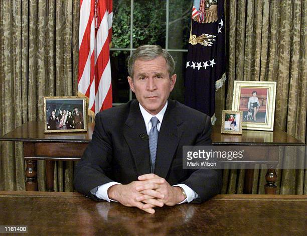 US President George W Bush sits at his desk in the Oval Office after addressing the nation about the terrorist attacks on New York and Washington DC...