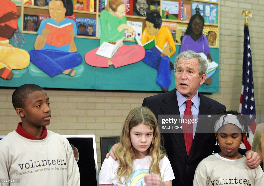 US President George W. Bush (2nd R) speaks on Martin Luther King, Jr. Day, as he stands with young children after helping teach a lesson on the importance of the day to the children during a tour of the Martin Luther King, Jr. Memorial Library in Washington, DC, 21 January 2008.