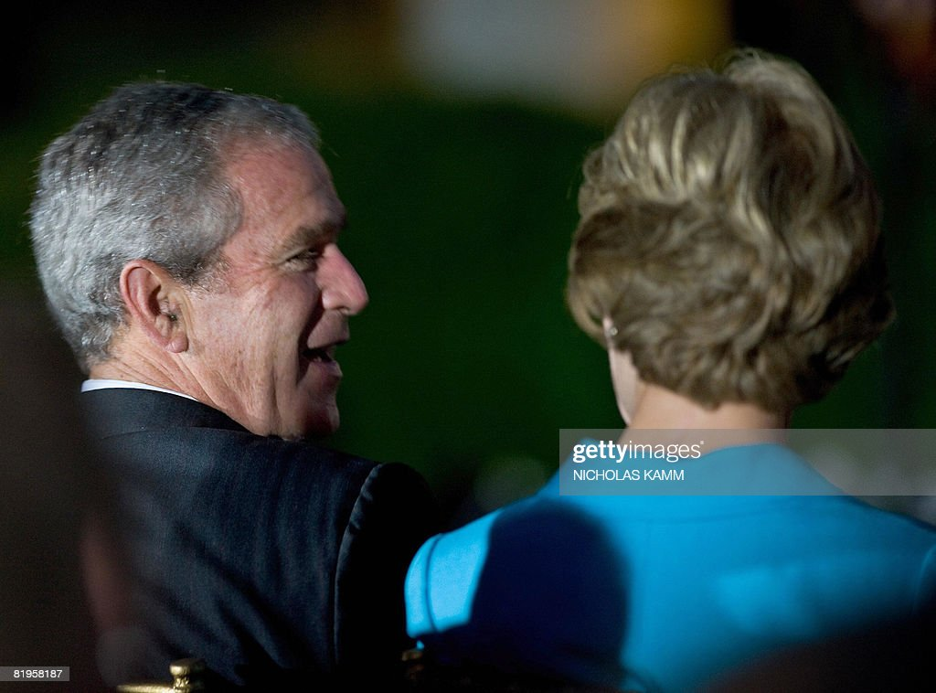 US President George W. Bush speaks to his wife Laura Bush during a performance by country singer Kenny Chesney in the Rose Garden at the White House on July 16, 2008. AFP PHOTO / Nicholas KAMM