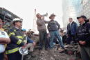 S President George W Bush speaks to rescue workers firefighters and police officers from the rubble of Ground Zero September 14 2001 in New York City...