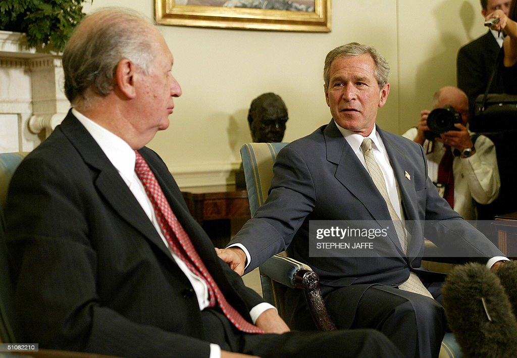 US President George W. Bush (R) speaks with Chile's President Ricardo Lagos (L) in the Oval Office of the White House 19 July 2004 in Washington, DC. Bush and Lago were to discuss democracy and trade in Latin American, notably on the free trade agreement between the two countries that took effect 01 January. Since the deal, Chile's exports to the United States have jumped by 13 percent, while US exports to Chile rose 13 percent. AFP Photo/Stephen JAFFE